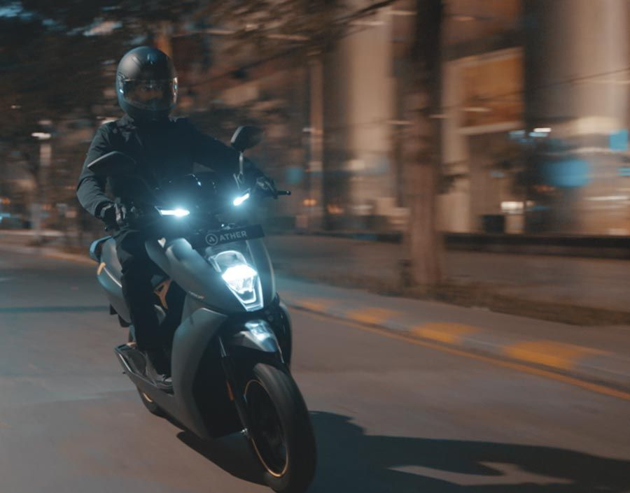 A person is driving the Ather 450x through the streets of Bangalore at night.