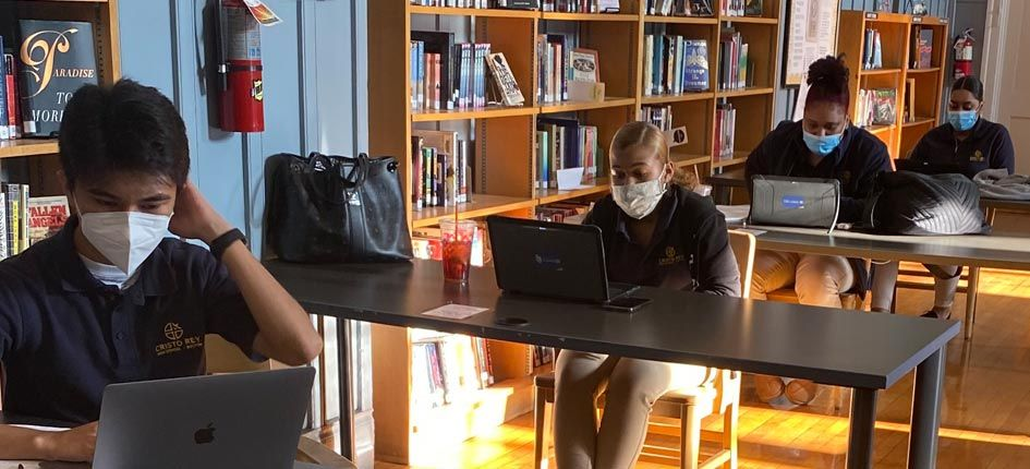 Four students, one boy and three girls, studying in a library. Each is at their own desk, 6 feet apart, wearing masks and working on a laptop.