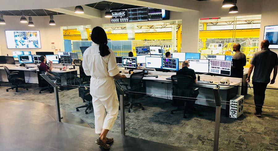 The control room at TAE. In the background, the reactor is visible though large windows. People are seated at desks with multiple monitors in the room, and a woman stands in the foreground.