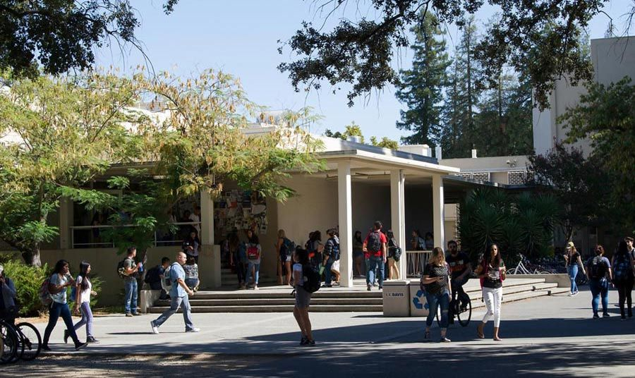 University students walking to class on a sunny day, outside of Young Hall on the UC Davis campus.